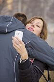 image of she-male  - Boy hugging a girl while she looks at her smartphone outdoors - JPG
