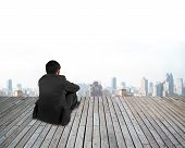 foto of knee  - Rear view of black suit businessman with hands holding his knee sitting on wooden floor and urban scene background - JPG