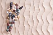 image of wavy  - Creative colorful pebble map of Argentina using smooth waterworn agate and quartzite stones on decorative beach sand with a wavy pattern depicting ripples with copyspace for a travel template - JPG