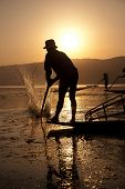stock photo of fishermen  - Fisherman hit water before catching the fishes into his traditional fishing equipment Inle lake Myanmar - JPG