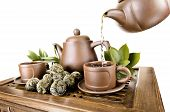 stock photo of loam  - horizontal photo of the clay teapot tea flow in cup on white background isolated tea ceremony - JPG