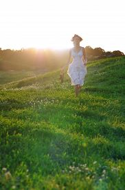 stock photo of rune  - Girl runing on a green summer meadow on a sunny summer day - JPG