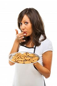 stock photo of finger-licking  - Young woman holding a tray with homemade chocolate cookies licking her finger and looking at camera - JPG