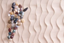 stock photo of agate  - Creative colorful pebble map of Argentina using smooth waterworn agate and quartzite stones on decorative beach sand with a wavy pattern depicting ripples with copyspace for a travel template - JPG