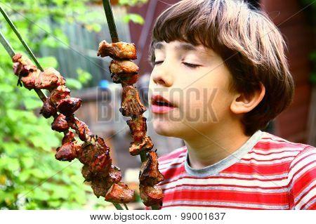 preteen boy smell shashlik meat on summer picnic