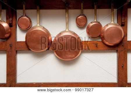 Vintage Copper Pans Hung On Wooden Shelf