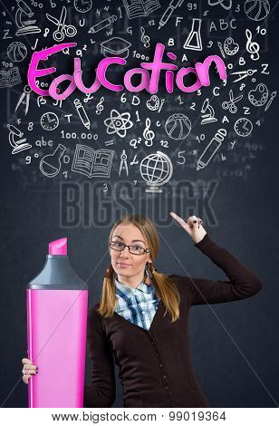 Schoolgirl with marker pointing in word education word
