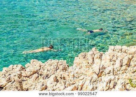 A Couple Snorkeling In The Crystal Clear Rocky Adriatic Sea