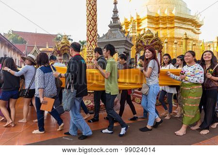 LAMPHUN, THAILAND, DECEMBER 31, 2014: Thai people are holding a long sacred cloth, in procession around the Wat Phra That Hariphunchai temple for celebrating the new year in Lamphun, Thailand