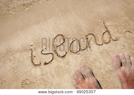 Conceptual island text hand written in sand on a beach on an exotic island background with feet for summer