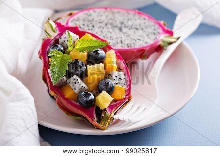 Tropical exotic salad inside a dragon fruit