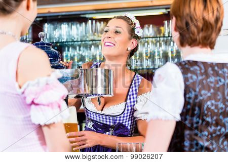 Innkeeper in Bavarian pub with customers