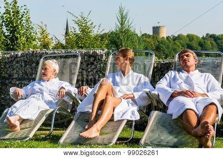 People relaxing on outdoor rest area of sauna