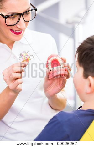 Female Orthodontist explaining boy braces