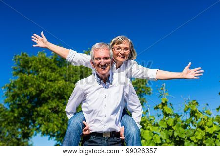 Senior man carrying woman piggyback, she is happy