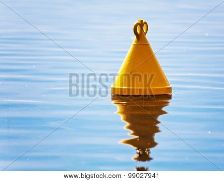 Single yellow buoy on a calm sea surface