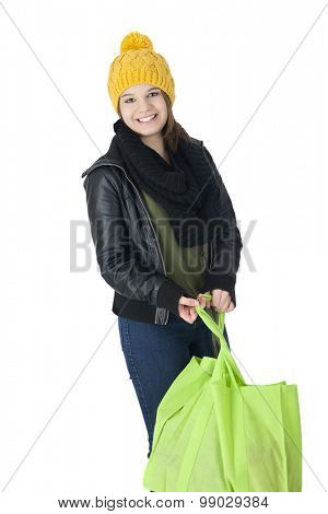 A pretty teen girl in yellow ski cap and black leather jacket happily carrying a cloth shopping bag.  On a white background.