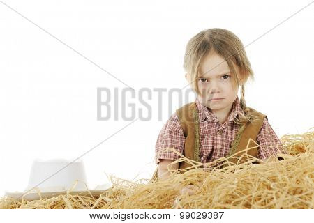 An angry preschool cowgirl sitting behind a pile of hay with her hat nearby.  On a white background with space for your text over her hat.