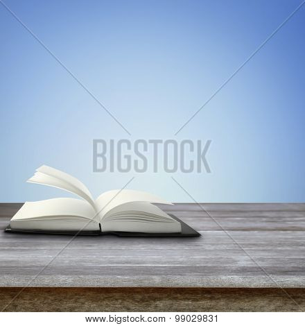 Open book on table in front of blue background