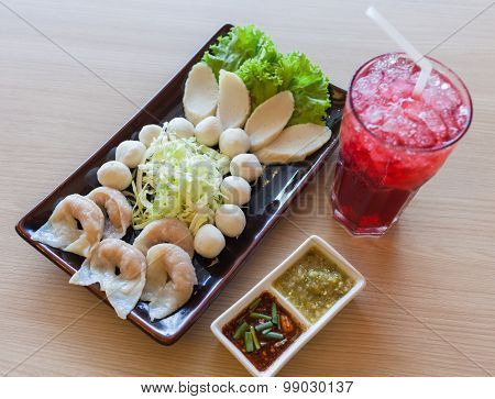 Mixed shrimp dumplings fish ball on dish with sauce and roselle water - shrimp dumplings focus.