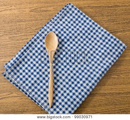 Wooden Spoon On A Blue Checked Towel