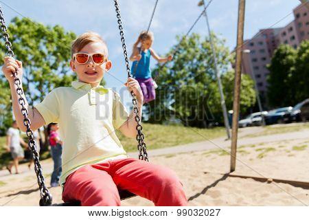 summer, childhood, leisure, friendship and people concept - two happy kids swinging on swing at children playground