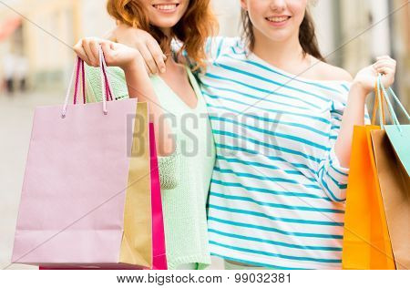 vacation, sale, leisure, consumerism and friendship concept - close up of happy young women or teenage girls with shopping bags on city street