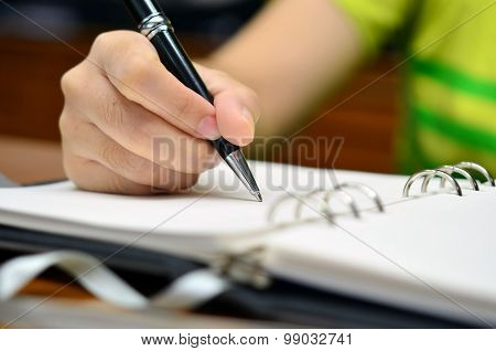 Hand writes on a book with a pen (Selective focus) - Business or education note