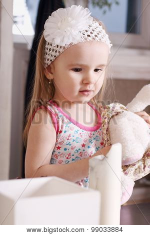 Little Cute Blond Girl With White Headband Holding Stuffed Toy