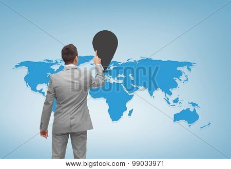 business, people and location concept - businessman pointing finger to mark on world map over blue background from back