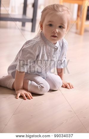 Little Cute Blond Girl In Striped Shirt Sitting On Wooden Floor