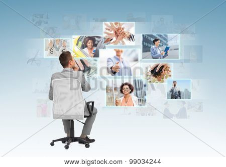 business, people, design and choice concept - businessman sitting in office chair and looking at different images over blue background from back