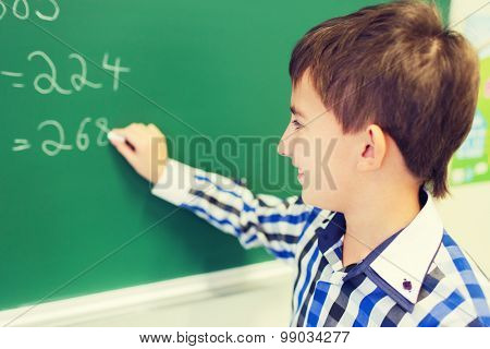 education, elementary school, learning, math and people concept - little smiling schoolboy writing numbers on green chalk board in classroom