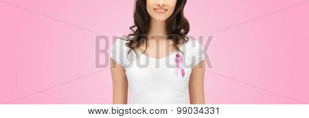 healthcare, people, charity and medicine concept - smiling young woman in t-shirt with breast cancer awareness ribbon over pink background