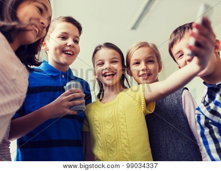 education, elementary school, drinks, children and people concept - group of school kids with smartphone and soda can taking selfie in corridor