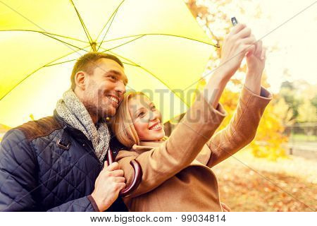 love, relationship, family, technology and people concept - smiling couple making selfie in autumn park