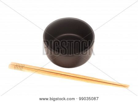 Black Ceramic Bowl With Wooden Shopsticks Isolated