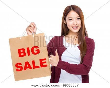 Young Woman hold with shopping bag and thumb up for showing big sale