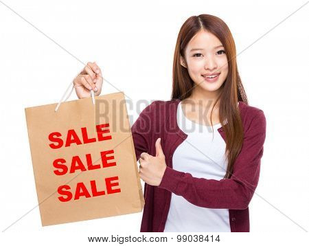 Young Woman hold with shopping bag and thumb up for showing three sale word