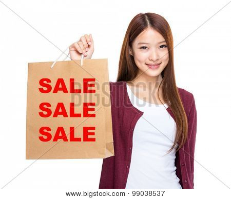 Woman hold with shopping bag and showing three sale word
