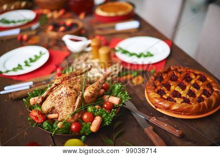 Baked chicken and berry pie on table