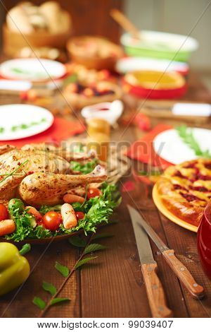 Wooden table with roasted chicken and pie