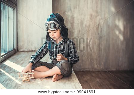 Little boy with plane indoors