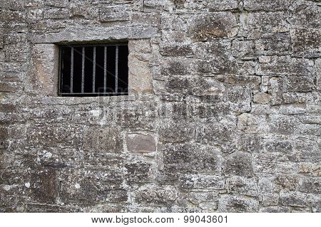 Medieval jail wall with a grill window.