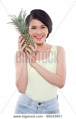 Girl with ripe pineapple