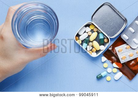 Pills With Hand Holding Drinking Water