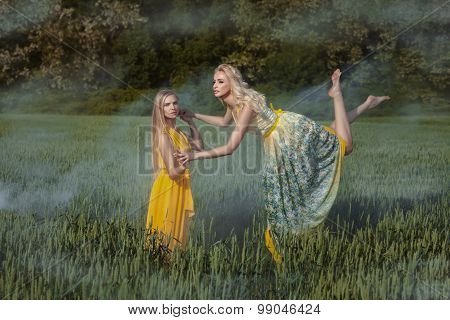 Two Girls In The Field. One Girl Levitates.