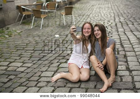 Two hilarious teenage girls are doing selfie on the phone sitting on the pavement.