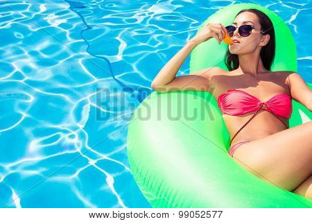 Portrait of a beautiful woman eating orange while lying on air mattress in swimming pool