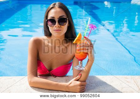 Portrait of a cute woman standing in swim pool and holding cocktail outdoors